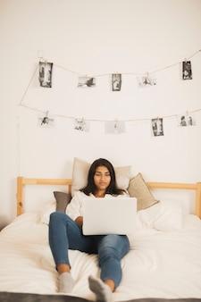 Hermosa mujer mirando en la computadora portátil en la cama