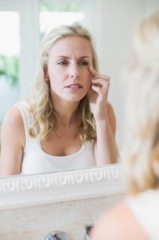 Hermosa mujer mirando a sí misma en el espejo en el baño