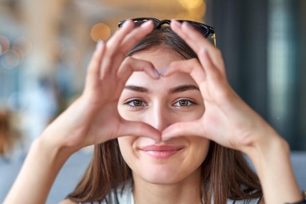 Hermosa mujer mirando a través del gesto de corazón hecho con las manos