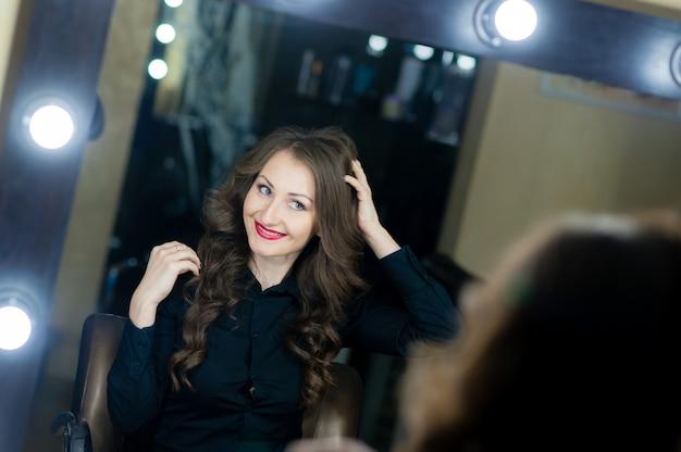 Hermosa mujer mirándose en el espejo