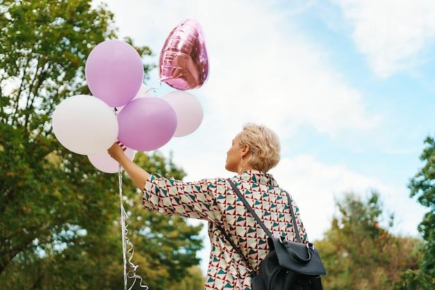 Hermosa mujer con mochila caminando feliz con globos rosas en el parque. libertad y concepto de mujer sana.