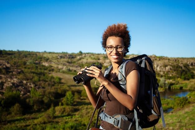 Hermosa mujer con mochila sonriendo, sosteniendo binoculares