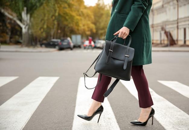 Hermosa mujer de moda cruzando la carretera