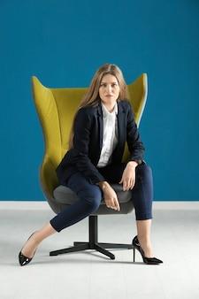 Hermosa mujer de moda en traje elegante sentado en un sillón contra la superficie de color