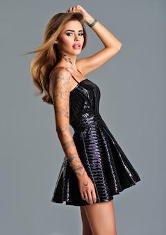 Hermosa mujer de moda en vestido negro con un tatuaje en la mano. retrato de moda de niña modelo de mujer joven con cabello largo posando en el estudio.