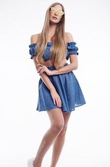 Hermosa mujer modelo con cabello largo posando en vestido azul de moda