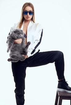 Hermosa mujer modelo en un chándal posando con un gato pedigrí gordo