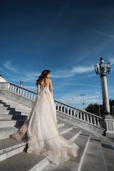 Hermosa mujer modelo con cuerpo perfecto en vestido de novia de lujo se encuentra con la espalda en las escaleras y posando con cielo azul en el fondo