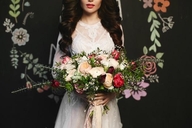 Hermosa mujer modelo morena con elegante peinado en el elegante vestido de encaje con un gran ramo de flores exóticas de lujo en sus manos, posando en fondo negro