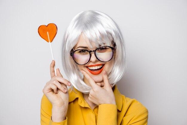 Hermosa mujer modelo con una piruleta de corazón en la mesa en una camiseta amarilla plantea diferentes emociones.