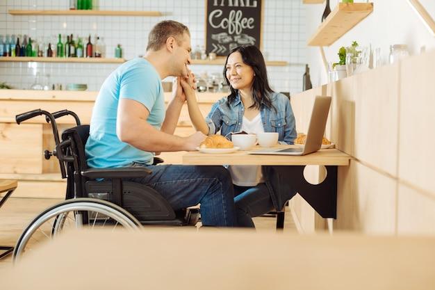 Hermosa mujer morena alegre y un apuesto hombre discapacitado sonriente sentado en la mesa en un café y escuchando música y tomando café