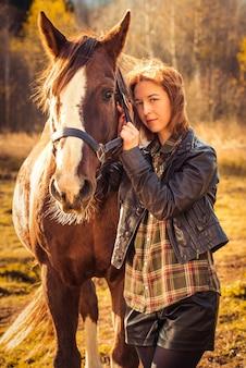 Hermosa mujer morena y caballo afuera en la naturaleza otoñal