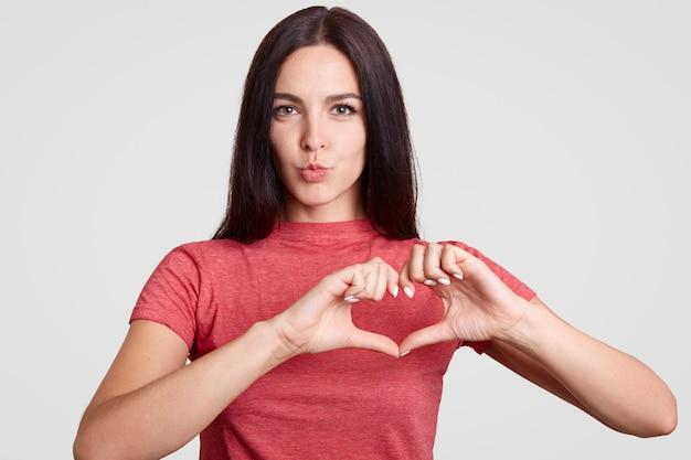 Hermosa mujer morena en camiseta roja casual hace el símbolo del corazón con ambas manos