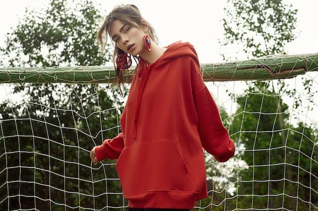 Hermosa mujer morena con capucha roja de moda en el campo de deportes