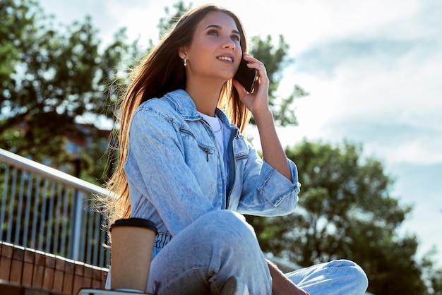Hermosa mujer morena se comunica con amigos mediante teléfono móvil.