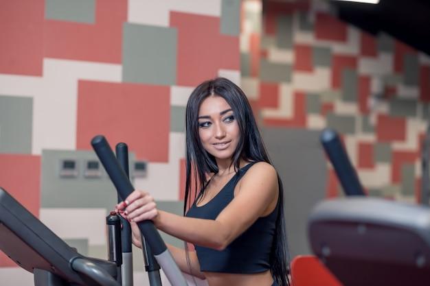 Hermosa mujer morena deportiva haciendo ejercicio con una máquina elíptica junto al hombre en forma y sonriendo a él durante el entrenamiento en el gimnasio moderno