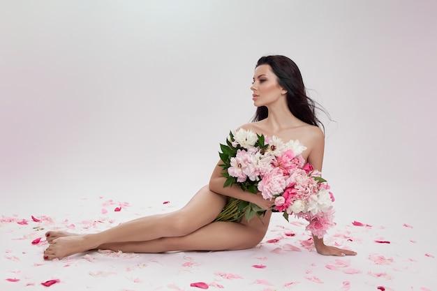 Hermosa mujer morena desnuda con flores de peonía