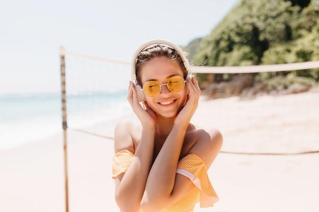 Hermosa mujer morena disfrutando de la canción con los ojos cerrados en la playa. tiro al aire libre de chica encantadora en auriculares blancos escalofriante en la playa salvaje.