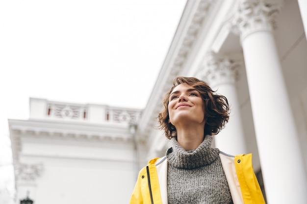 Hermosa mujer morena disfrutando mientras disfruta de puntos de referencia de pie delante del antiguo edificio con amplia sonrisa