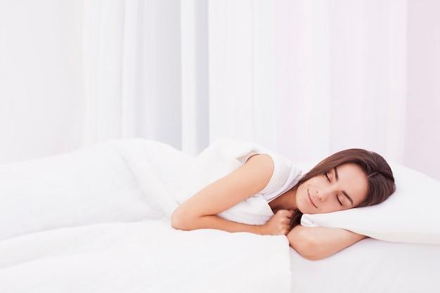 Hermosa mujer morena está durmiendo en una gran cama blanca