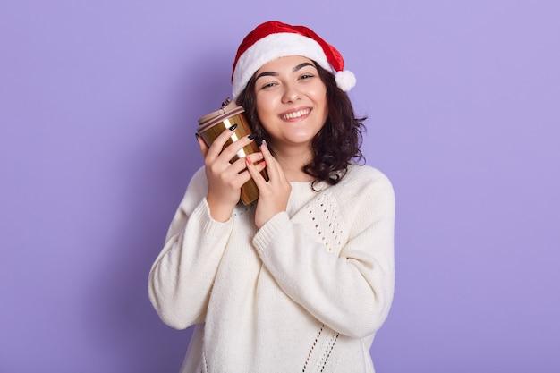 Hermosa mujer morena feliz con sombrero de santa y suéter de punto con taza termo, disfrutando de café o té caliente, posando aislada sobre pared lila, dama con cabello ondulado y manicura.
