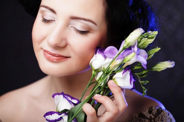 Hermosa mujer morena con flores lilas