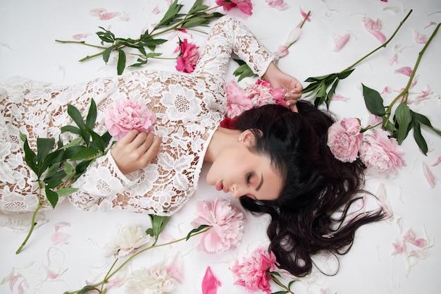 Hermosa mujer morena con flores de peonía