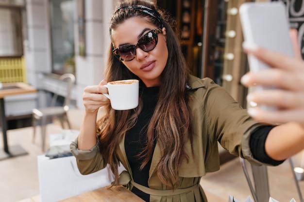 Hermosa mujer morena con gafas de sol tomando café y tomando una foto de sí misma en fin de semana