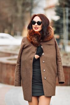 Hermosa mujer morena glamorosa en un elegante vestido verde y abrigo de piel con una piel esponjosa, guantes y elegantes gafas de sol al aire libre. mujer joven con elegante cabello largo y oscuro y maquillaje de moda