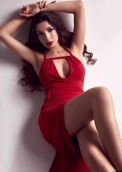 Hermosa mujer morena joven con el pelo rizado en vestido rojo