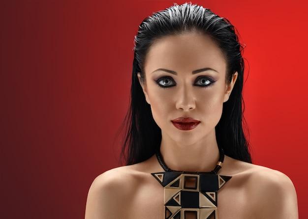 Hermosa mujer morena joven posando en el fondo rojo de estudio