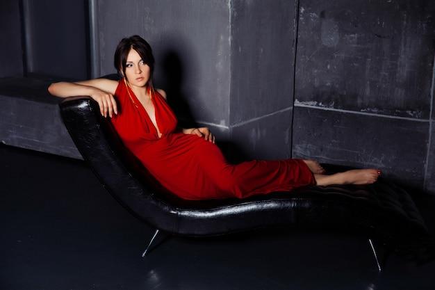 Hermosa mujer morena joven en vestido de noche largo rojo posando en el sofá de cuero negro en el interior oscuro del grunge