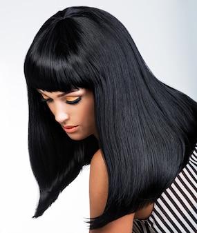 Hermosa mujer morena con largo cabello lacio negro posando en el estudio