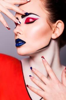 Hermosa mujer morena con maquillaje creativo del arte pop y estilo de uñas geométrico, líneas negras y ojos cerrados