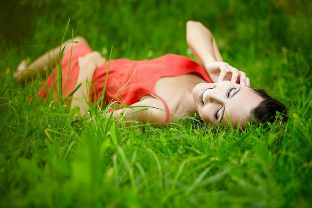 Hermosa mujer morena modelo tumbado en verano verde hierba brillante en el parque con maquillaje en vestido rojo.