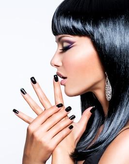 Hermosa mujer morena con uñas negras y maquillaje de ojos de moda