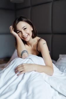 Hermosa mujer morena de pelo largo en cama blanca en suave luz de la mañana bajo el edredón