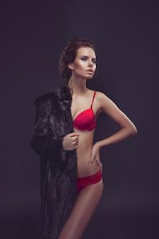 Hermosa mujer morena de pelo largo sexy en lencería negra y abrigo de piel posando