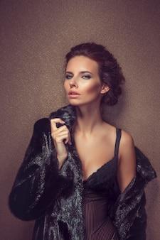 Hermosa mujer morena de pelo largo sexy en ropa interior negro y abrigo de piel posando en el. la belleza de la cara y el cuerpo. fotos tomadas en un