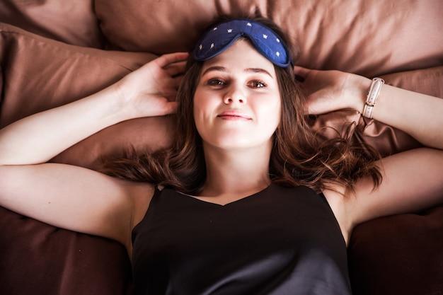 Una hermosa mujer morena en pijama negro y con un antifaz para dormir en su rostro se encuentra y mira a la cámara. la niña se puso las manos debajo de la cabeza.