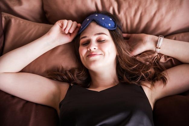 Una hermosa mujer morena en pijama negro y un antifaz para dormir en su rostro yace con los ojos cerrados.