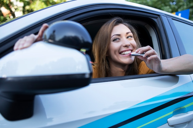 Hermosa mujer morena sentada en el coche y poniéndose guapa usando lápiz labial aplicando maquillaje