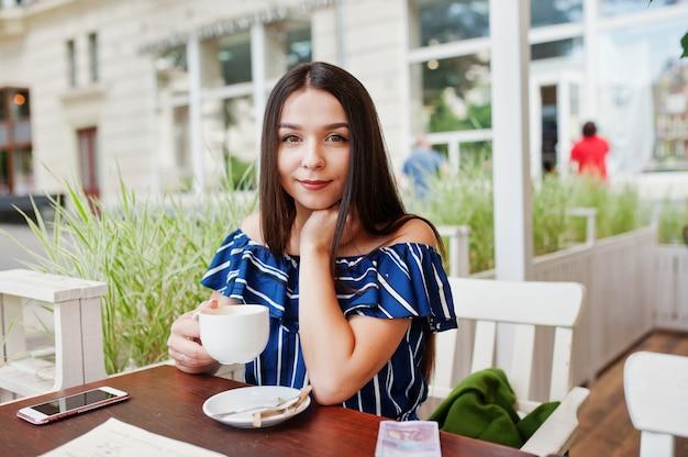 Hermosa mujer morena sentada en la mesa de café con taza de café.