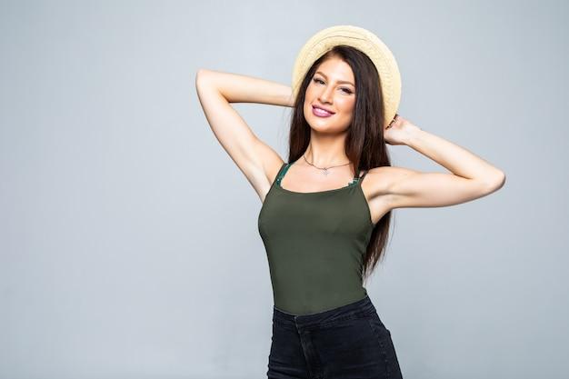 Hermosa mujer morena sonriente en sombrero de paja aislado en blanco