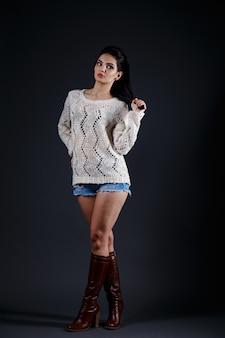 Hermosa mujer morena en suéter beige y pantalones cortos azules