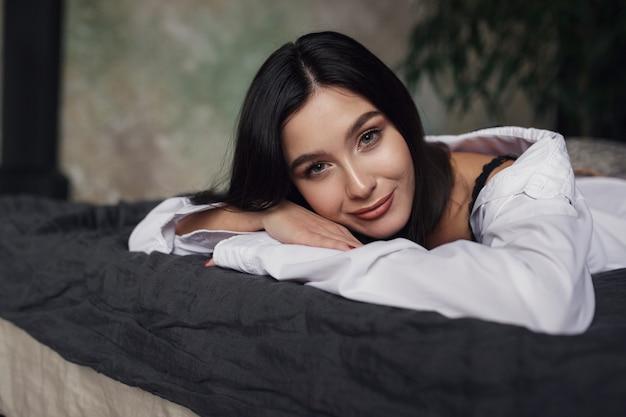 Hermosa mujer morena vestida con lencería de moda, en la cama en una habitación oscura.