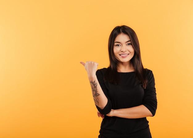 Hermosa mujer morena vistiendo ropa negra con tatuaje en el brazo apuntando con el dedo a un lado en texto copyspace o producto con sonrisa sincera, aislado sobre fondo amarillo