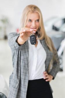 Hermosa mujer mostrando en las llaves de tiro medio de coche