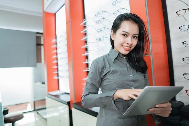 Una hermosa mujer muestra un catálogo de productos de anteojos disponibles después de hacerse un examen de la vista en una clínica oftalmológica.