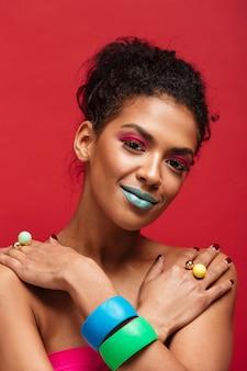 Hermosa mujer mulata semidesnuda con maquillaje de moda y accesorios coloridos poniendo las manos cruzadas sobre los hombros, sobre la pared roja